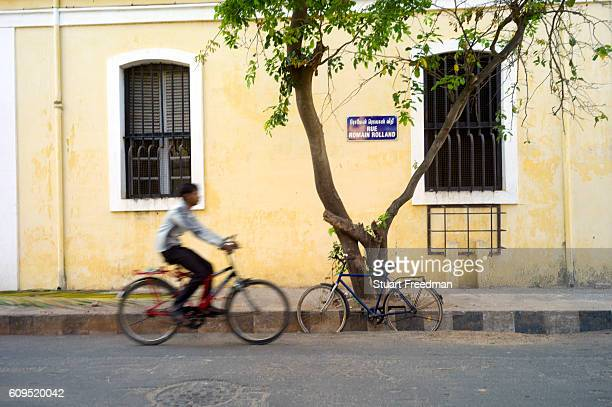 A man cycles past a bicycle and tree on Rue Romain Rolland Pondicherry India Pondicherry is a Union Territory of India and was a French territory...