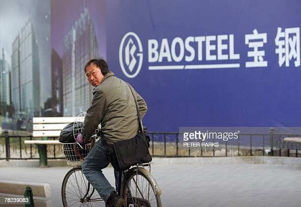 A man cycles past a bilboard advertising China's largest steel producer Baosteel Group in Beijing 04 December 2007 Baosteel Group is likely to launch...