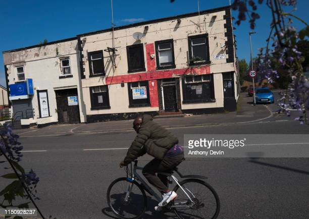 Man cycles past a boarded-up public house decorated with the flag of Saint George on May 22, 2019 in Manchester, England.