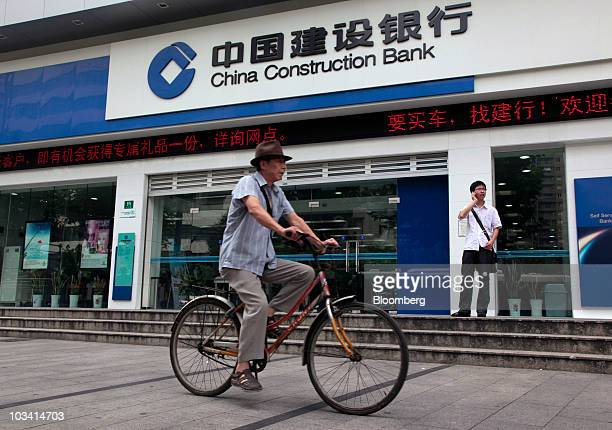 A man cycles past a branch of China Construction Bank Corp in Shanghai China on Tuesday Aug 17 2010 China Construction Bank Corp is the country's...