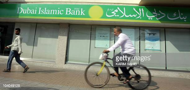 A man cycles past a branch of Dubai's Islamic Bank in the Gulf emirate on September 03 2010 Most banks in the United Arab Emirates an important...