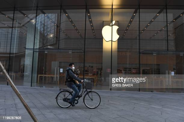 A man cycles past a closed Apple store in Beijing on February 8 2020 The death toll from China's coronavirus outbreak soared to 722 on February 8...
