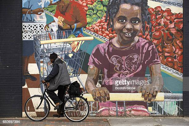 Man cycles past a colorful mural on Washington Street in Boston's Roxbury neighborhood on Feb. 21, 2016.