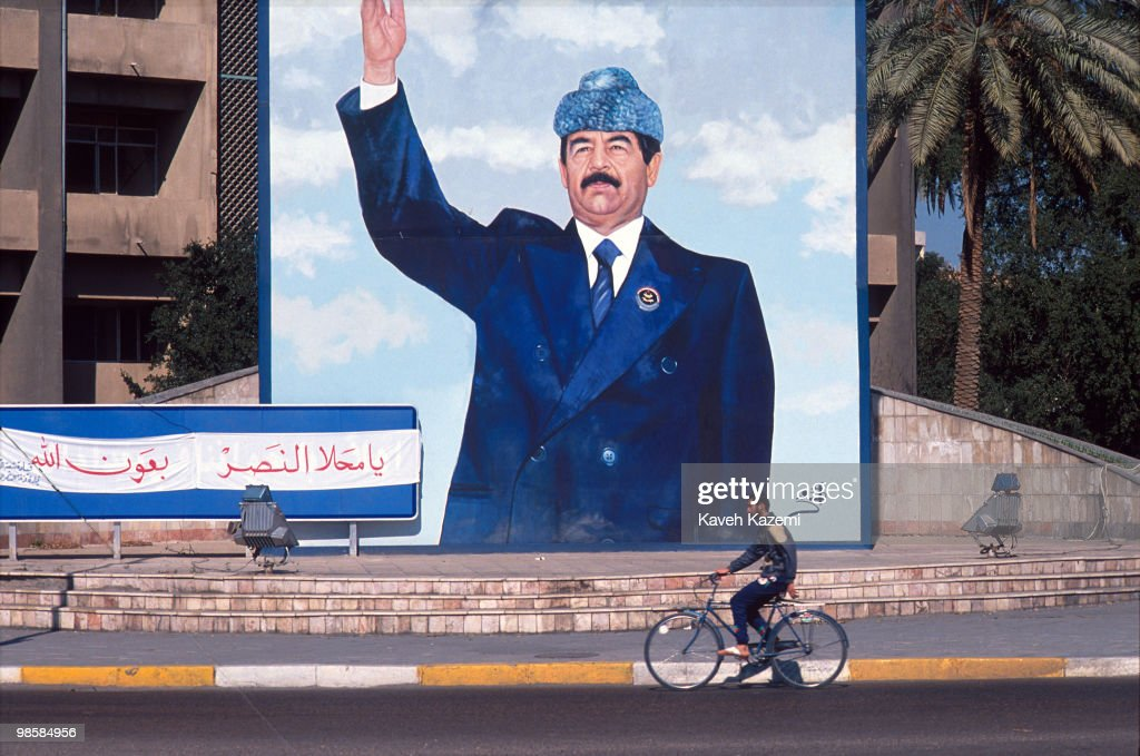 a man cycles past a huge mural of saddam hussein on the corner of a
