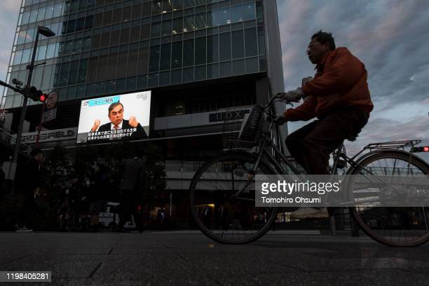 A man cycles past a monitor displaying a news broadcast on former Nissan Motor Co Chairman Carlos Ghosn on January 09 2020 in Tokyo Japan Ghosn was...