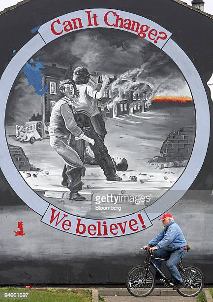 A man cycles past a new mural in the Shankill area of west Belfast UK Tuesday March 27 2007 The leaders of Northern Ireland's two main political...