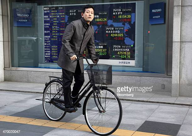 A man cycles past an electronic monitor displaying the closing figure of the Nikkei 225 Stock Average outside a securities firm in Tokyo Japan on...