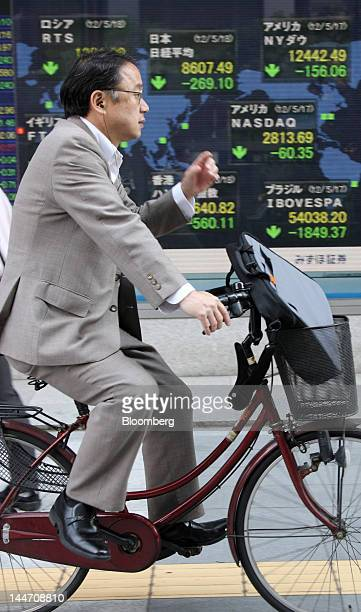 A man cycles past an electronic stock board in Tokyo Japan on Friday May 18 2012 Japanese stocks fell with the Topix Index headed for the longest...