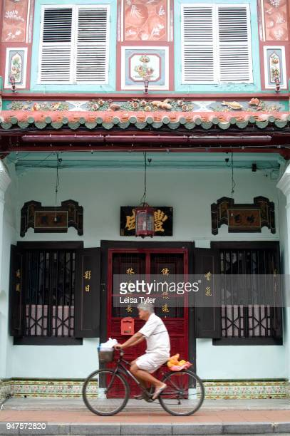 A man cycles past an old Chinese shop house or terrace house in Malacca Malaysia