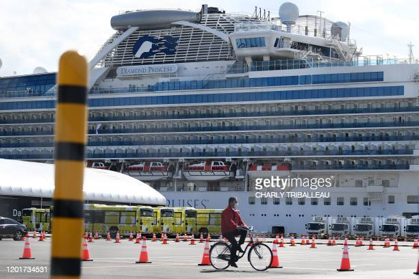 A man cycles past city buses lined up to transport the first batch of passengers disembarking from the Diamond Princess cruise ship in quarantine due...