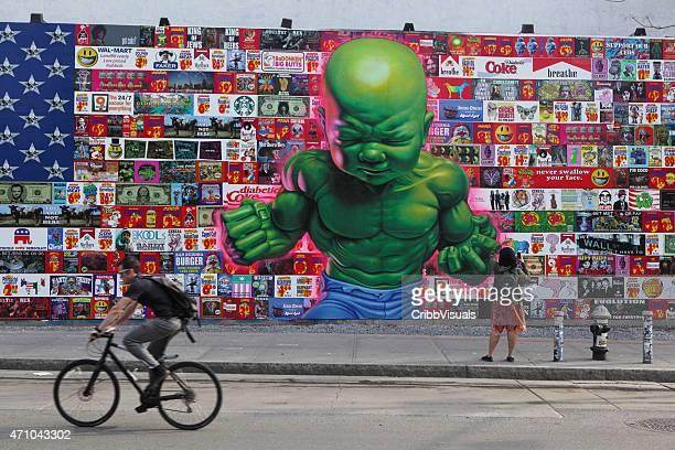 uomo cicli dopo enormi murales colorati a houston street new york - murale foto e immagini stock