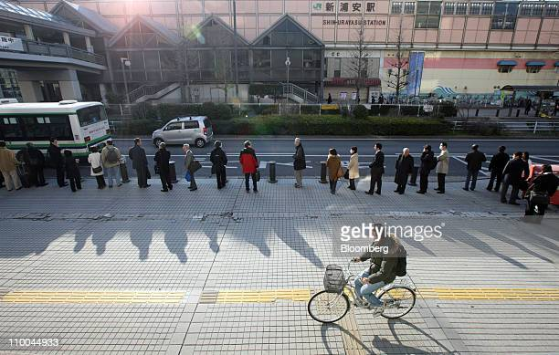 A man cycles past morning commuters waiting in line for a bus outside an East Japan Railways Co train station after Tokyo Electric Co announced the...
