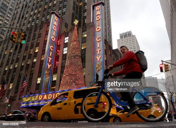 A man cycles past Radio City Music Hall dressed up with Christmas decorations along 6th Avenue on December 5 2017 in New York City