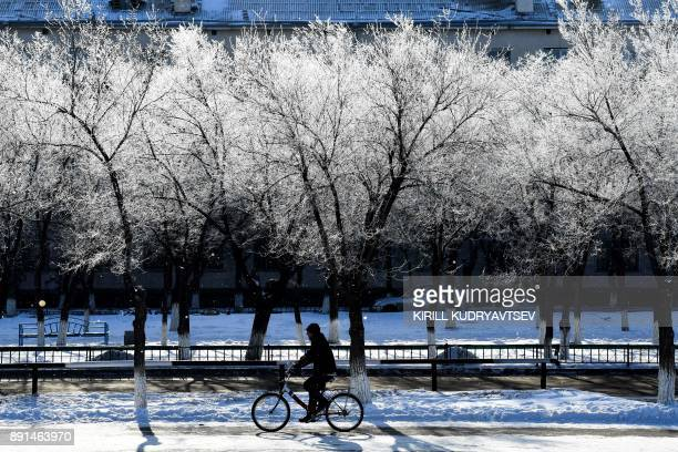 A man cycles past snowcovered trees in Baikonur city near the Russian leased Kazakh Baikonur cosmodrome on December 13 2017 The temperature in...