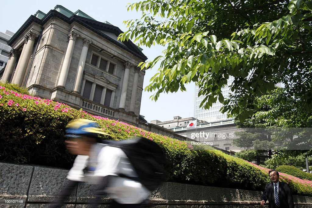 A man cycles past the Bank of Japan headquarters in Tokyo, Japan, on Friday, May 21, 2010. The Bank of Japan said it will provide one-year loans to banks to encourage lending and defeat deflation, and raised its assessment of the export-led recovery. Photographer: Kiyoshi Ota/Bloomberg via Getty Images