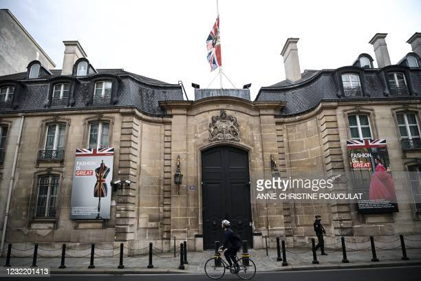 Man cycles past the British Embassy as he looks at the Britain's national flag, the Union Jack, flying at half-mast, in Paris on April 9, 2021 after...
