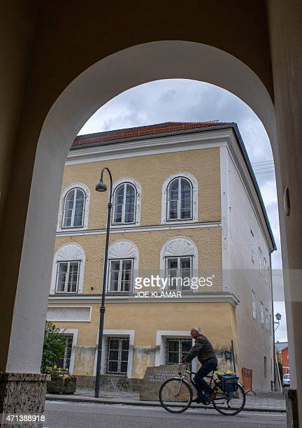 A man cycles past the house where Adolf Hitler was born in Braunau Am Inn Austria on April 18 2015 The weatherworn threestorey structure in the...