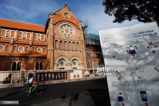 Man cycles past the Notre-Dame Cathedral Basilica of Saigon in Ho Chi Minh City on July 9 on the first day of the government imposed two-week...