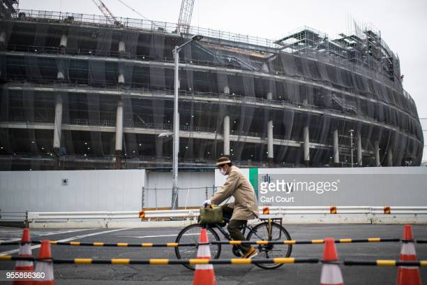 Man cycles past the under-construction New National Stadium, the main stadium for the upcoming Tokyo 2020 Olympic and Paralympic Games, on May 8,...