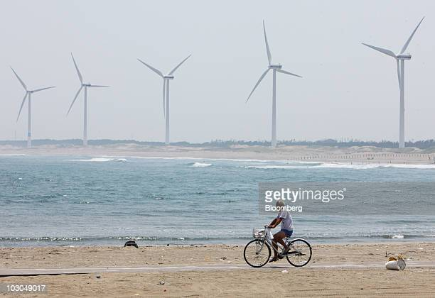 A man cycles past wind turbines at the Hasaki wind farm in Kamisu City Ibaraki Prefecture Japan on Friday July 23 2010 Japan is under pressure to...