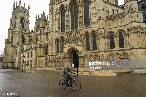 Man cycles past York Minster as the historic building closes its doors as the UK adjusts to life under the Coronavirus pandemic on March 18, 2020 in...