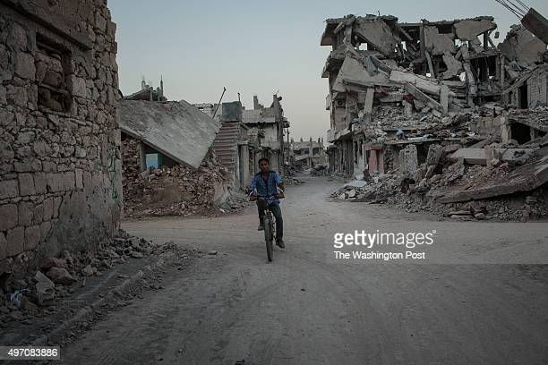 A man cycles through a heavily damaged neighborhood where they used to live in Kobane Syria targetted by a series of USled coalition airstrikes aimed...