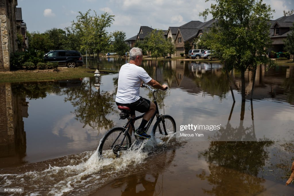 A man cycles through floodwater in the aftermath of tropical storm Harvey, in the Millwood subdivision of Fort Bend County, Texas, on Sept. 2, 2017.