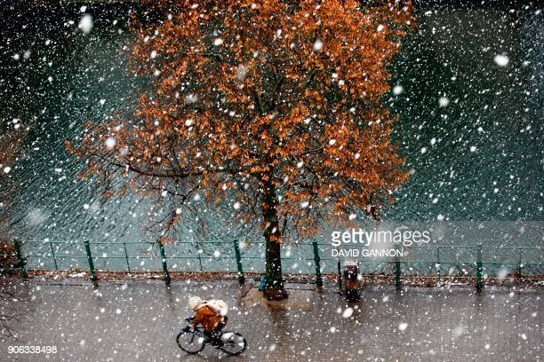 A man cycles through fresh snowfall in Berlin on January 18 2018 Weather forecasts predict a heavy storm and snow over Germany / AFP PHOTO / DAVID...