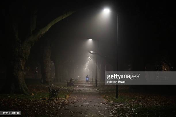 Man cycles through London Fields in the dark and mist during the second coronavirus national lockdown on November 7th 2020 Hackney, East London,...