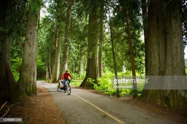 man cycling a scenic trail with his child - valley stock pictures, royalty-free photos & images