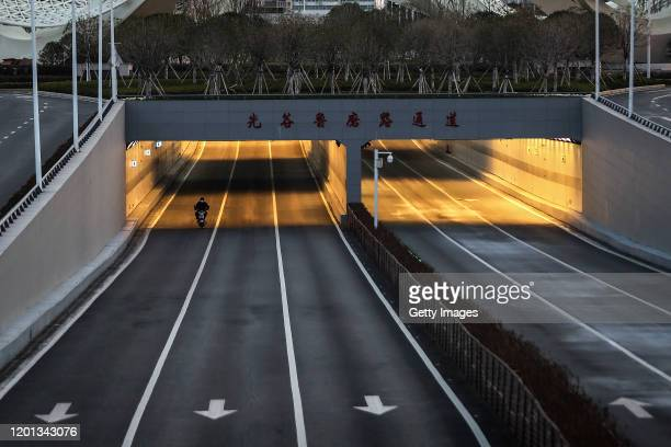 A man cycling bike in the empty street at Optical Valley on February 16 2020 in Wuhan Hubei province China Flights trains and public transport...