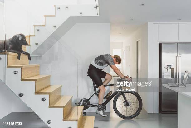 man cycling indoors on turbo trainer - home workout stock pictures, royalty-free photos & images