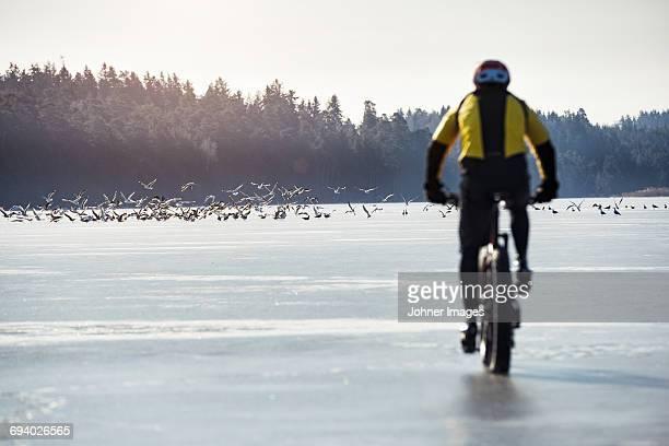 Man cycling on a frozen lake