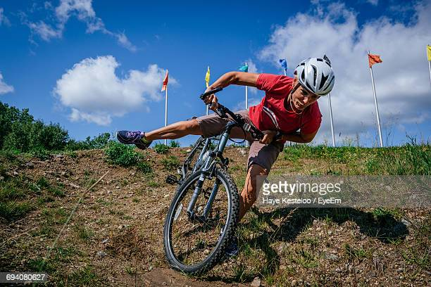 Man Cycling On Bicycle Against Sky