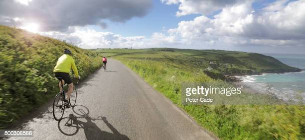 man cycling on coastal road - cornwall england stock pictures, royalty-free photos & images