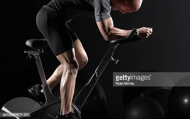 man cycling on exercise bike, side view - peloton stock pictures, royalty-free photos & images