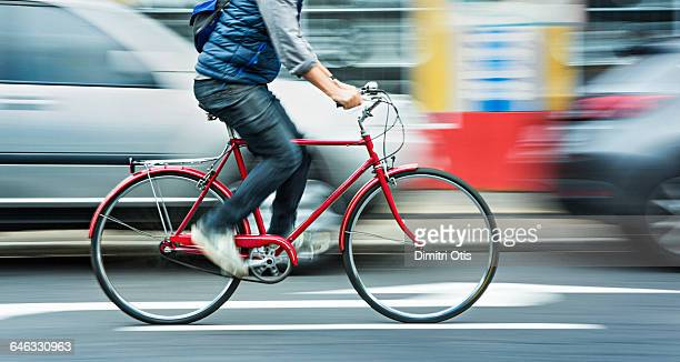 man cycling on red bicycle in street with movement - westen stock-fotos und bilder