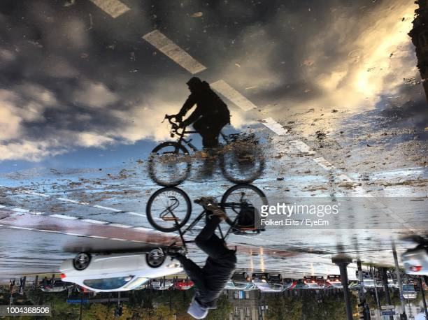 man cycling on road reflecting in puddle - extremwetter stock-fotos und bilder