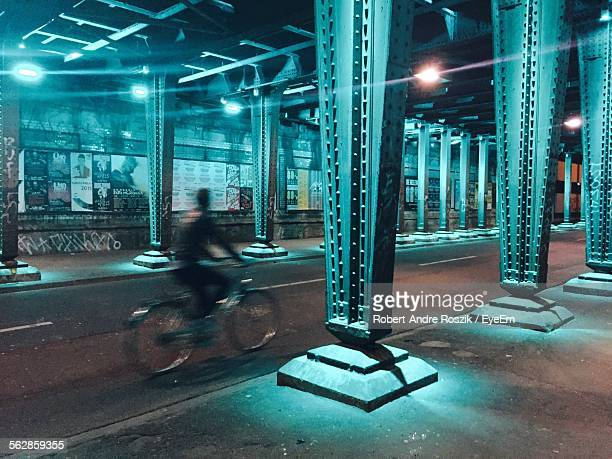 Man Cycling On Road Under Bridge