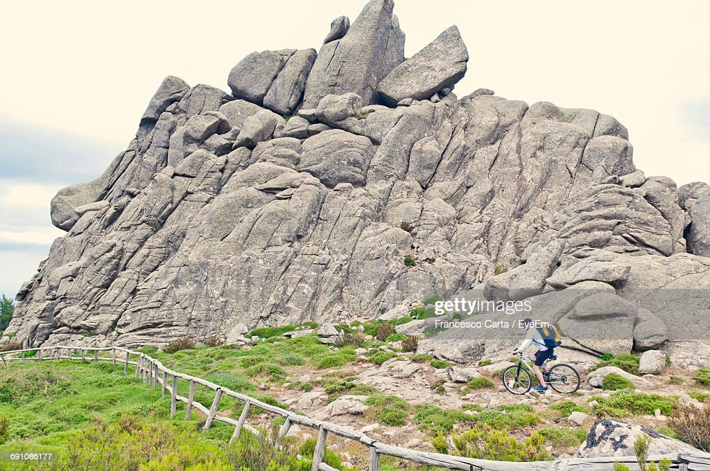 Man Cycling On Rocky Pathway By Mountain : Stock Photo