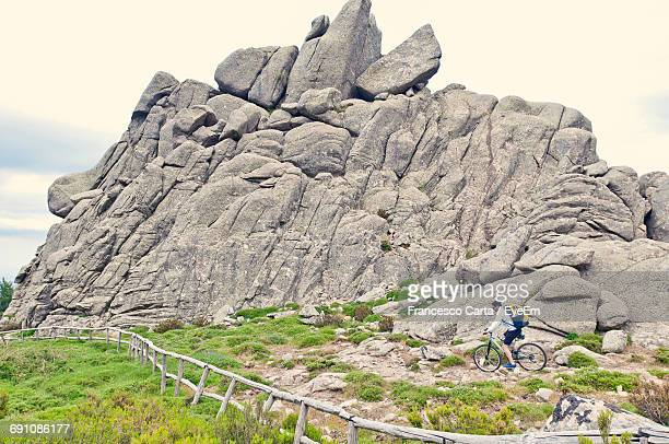 man cycling on rocky pathway by mountain - tempio pausania stock pictures, royalty-free photos & images
