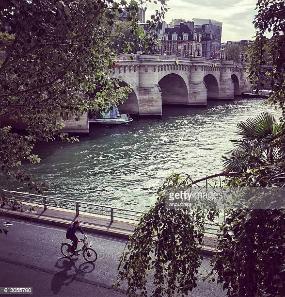 Man cycling on Seine riverbank in Paris, France