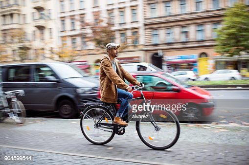 Man cycling on street in city during winter