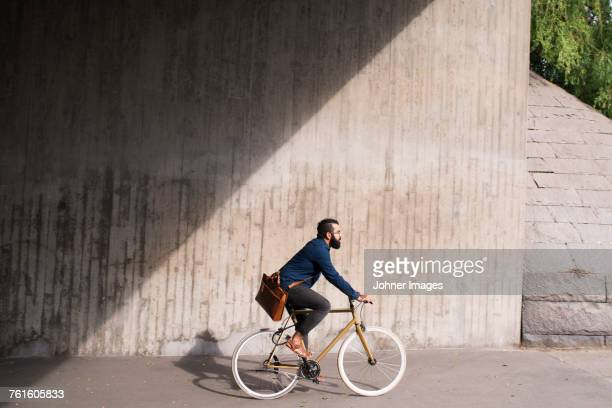 man cycling on street - radfahren stock-fotos und bilder