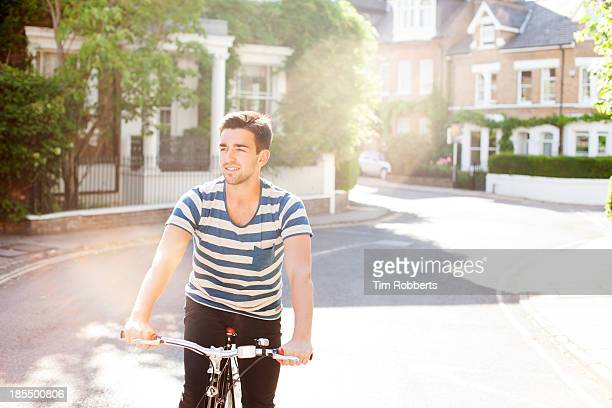 man cycling on streets - ボーダーシャツ ストックフォトと画像