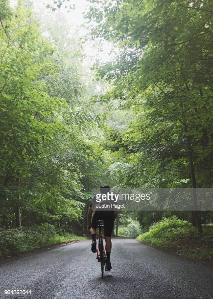 man cycling on woodland road - back stock pictures, royalty-free photos & images