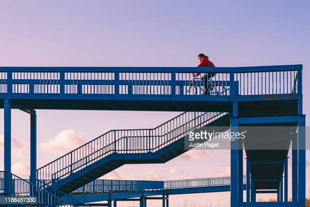 man cycling over pedestrian bridge - blue stock pictures, royalty-free photos & images