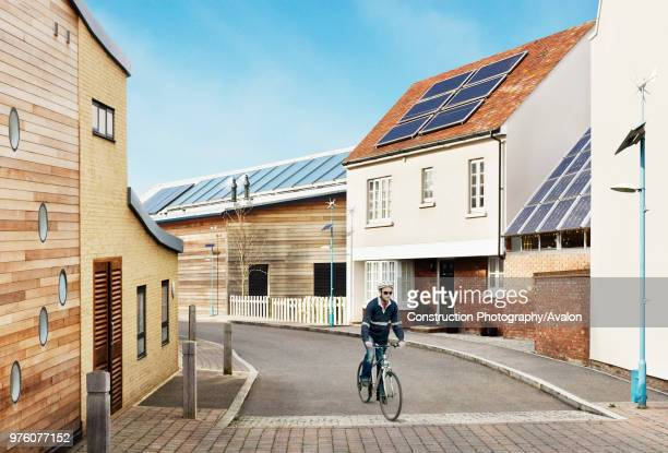 Man cycling Sustainable eco-friendly houses Eco Town, England, UK .