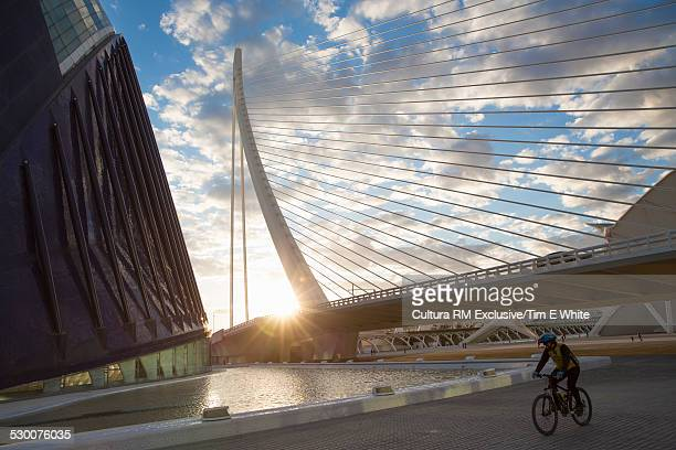 Man cycling through The City of Arts and Sciences, Valencia, Spain