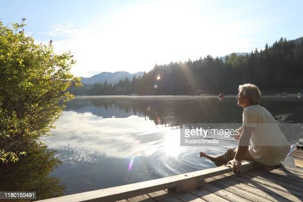 man dabbles voeten vanaf lakeside pier in de ochtend - meeroever stockfoto's en -beelden